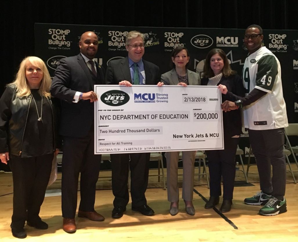 (from left to right) STOMP Out Bullying Founder and CEO Ross Ellis; Municipal Credit Union (MCU) Vice President of Business Development/Member Relations Corey Fernandes; New York Jets Team President Neil Glat; New York City Department of Education (DOE) Deputy Chancellor Elizabeth Rose; New York City DOE Chief Executive Officer, Office of Safety and Youth Development Lois Herrera and former Jets player Tony Richardson participate in the presentation of a $200,000 donation made on behalf of MCU and the New York Jets to the New York City DOE at Queens Metropolitan High School on Tuesday, February 13, 2018.