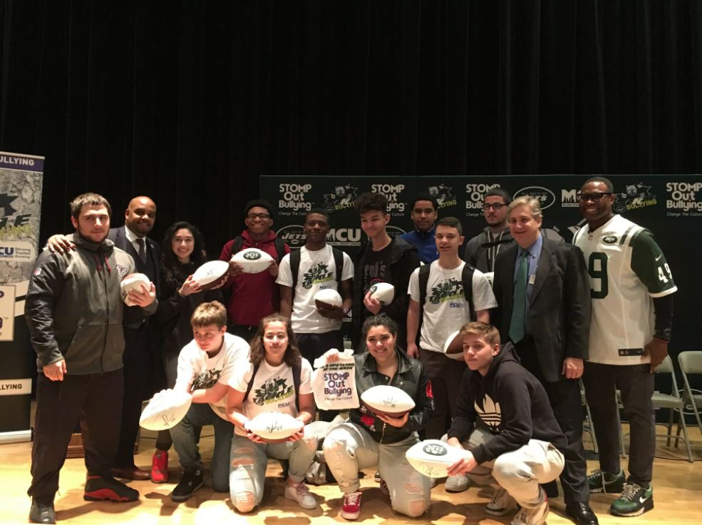 MCU Vice President of Business Development/Member Relations Corey Fernandes (second from left) and New York Jets Team President Neil Glat (second from right) stand with 16 Queens Metropolitan High School Students who were recognized throughout the Jets Upstander of the Week Program in the Fall and Winter of 2017. The students were again acknowledge for their efforts to combat bullying as a group during a STOMP Out Bullying school recognition event on Tuesday, February 13, 2018.