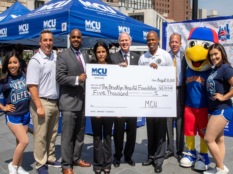 (from left to right) Brooklyn Cyclones Assistant General Manager Gary Perone, MCU Vice President of Business Development/Member Relations Corey Fernandes, Brooklyn Hospital Center's Dr. Madhavi Reddy, MCU Acting President/CEO Norman Kohn, Brooklyn Borough President Eric Adams and Brooklyn Hospital Center President Gary Terrinoni participate in a check presentation on the final day of the week-long MCU Shoot For A Cure at Brooklyn Borough Hall. MCU's donation will support free colon cancer screenings in high-risk areas.